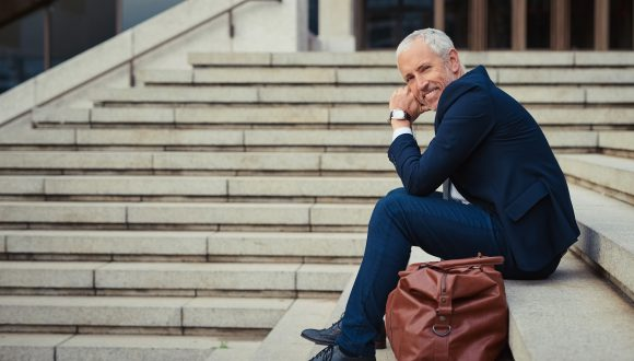 Portrait of a confident businessman sitting on the stairs outside his office building